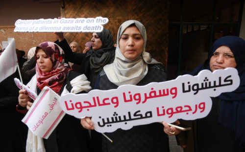 Palestinian Cancer patients take part in a protest to demand to travel for treatment