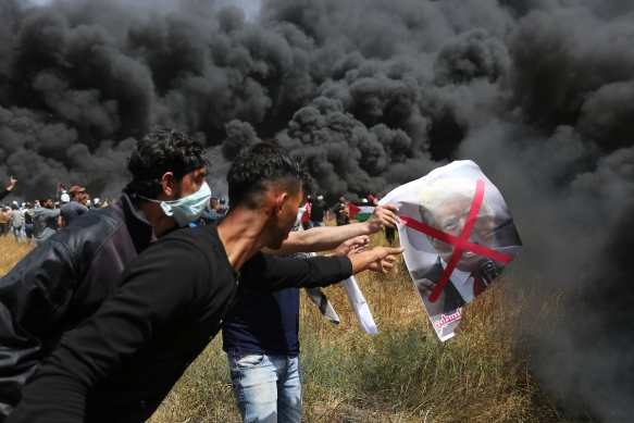 Palestinian protesters burn tires to protect themselves from shots of Israeli soldiers during clashes in a tent city protest at the Israel-Gaza border, demanding the right to return to their homeland, in Khan Younis in the southern Gaza strip