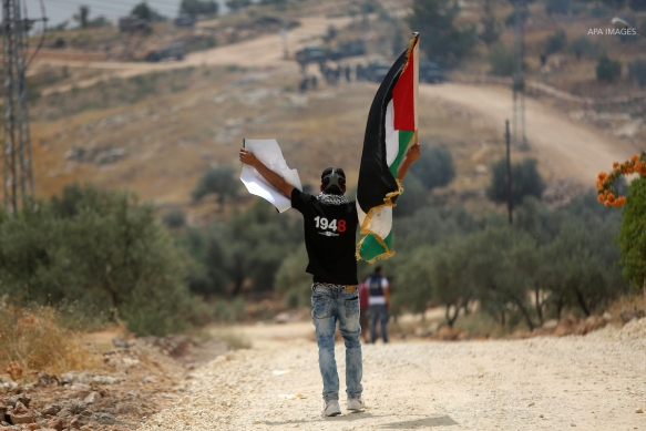 A Palestinian protester holds a Palestinian flag during clashes with Israeli troops at a protest ahead of Nakba day